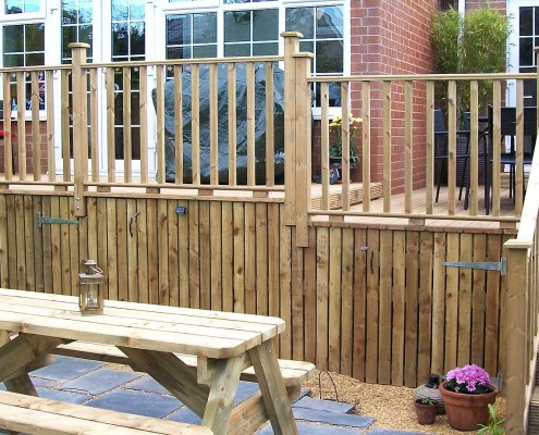 Complete raised decking with storage underneath and steps leading to the garden where a further outdoor eating area was created.