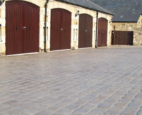 Large block paved driveway leading to garages at a converted farm building.