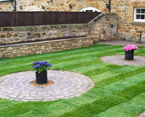 Small landscaped garden with block paving.