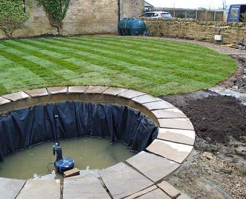 Work in progress - landscaped garden with a footpath leading to a fish pond.