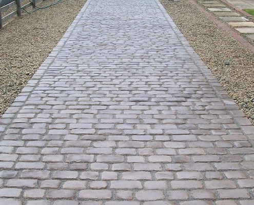 Block paved driveway with a small landscaped garden area.